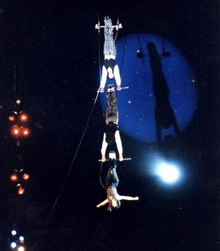 tres equilibristas suspendidos en columpio vertical