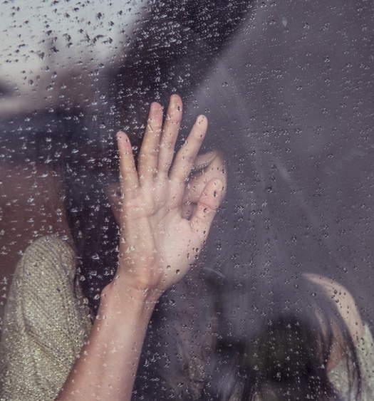 chica llorando apoyada con su mano en un cristal mojado by Milada Vigerova