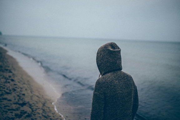 chica de espaldas andando por la playa con un jersei con capucha by Patryk Sobczak