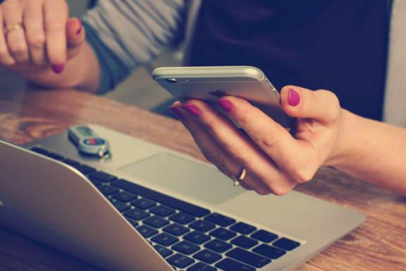manos de mujer con un móvil y un portátil