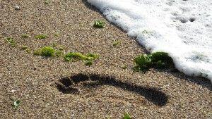 huella de un pie en la arena al lado de la orilla del mar
