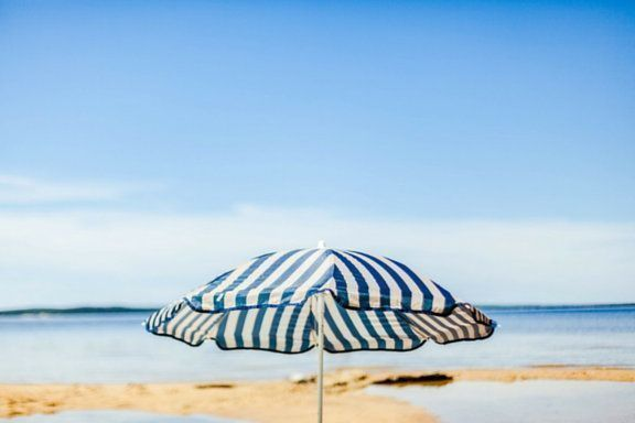 sombrilla de rayas azules en una playa by Antoine Beauvillain